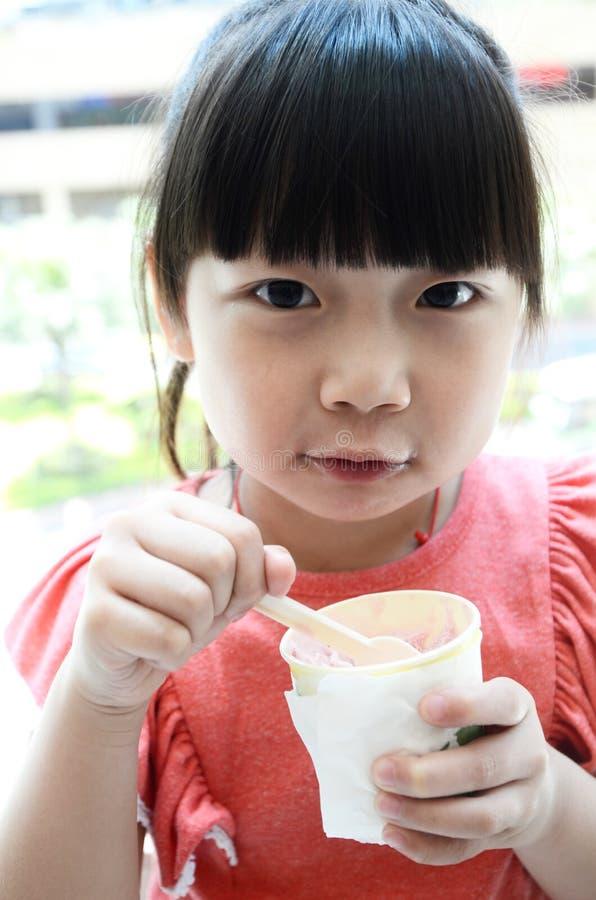 Criança asiática que come o gelado imagens de stock