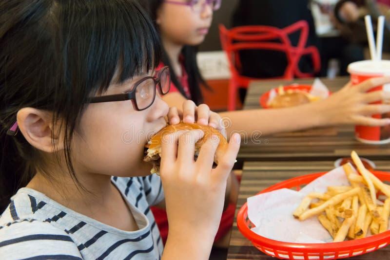 Criança asiática que come um Hamburger e batatas fritas foto de stock