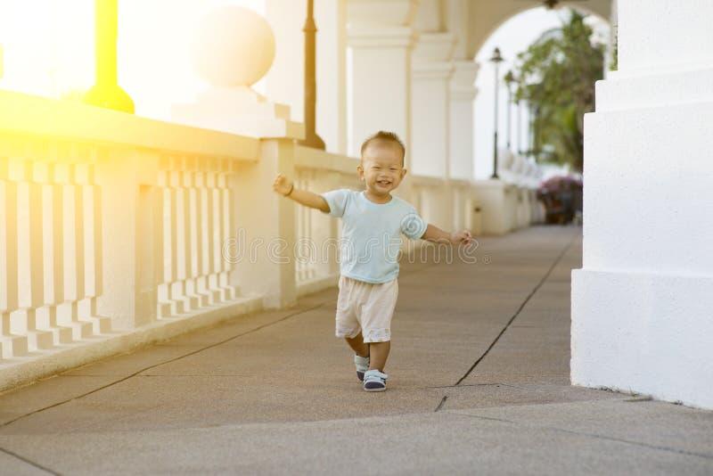 Criança asiática que corre em exterior fotografia de stock royalty free