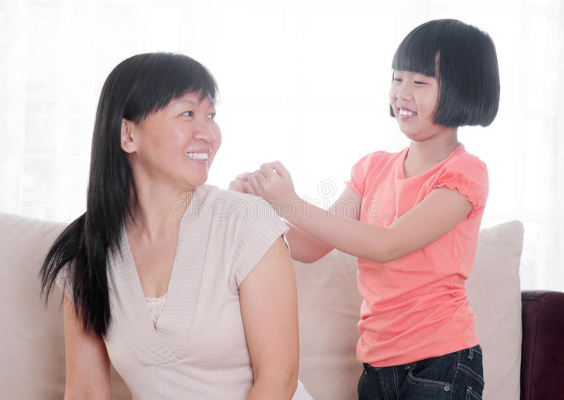 Criança asiática que faz a massagem do ombro a sua matriz foto de stock royalty free