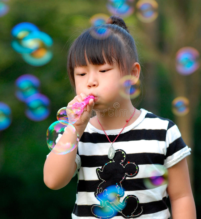 Criança asiática que joga bolhas de sopro foto de stock