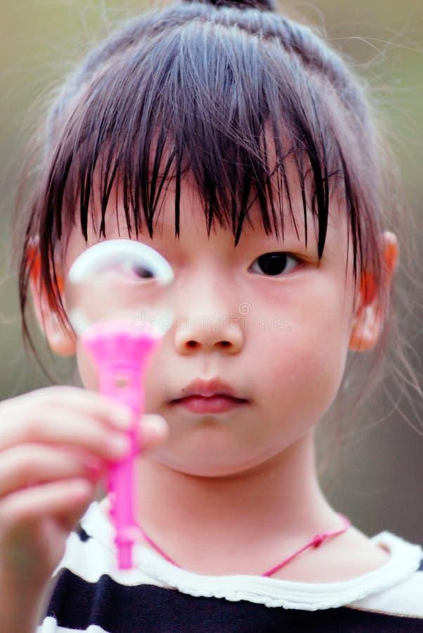 Criança asiática que joga bolhas de sopro imagem de stock
