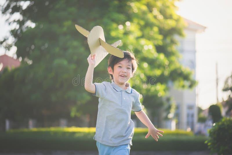 Criança asiática que joga o avião do cartão foto de stock