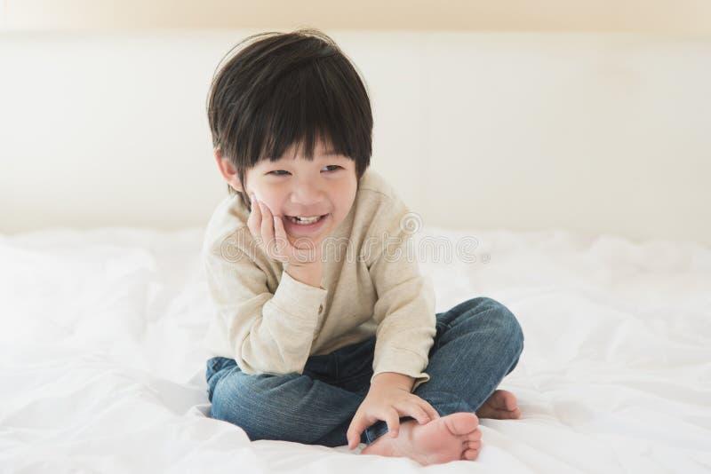 Criança asiática que senta-se na cama branca imagens de stock royalty free