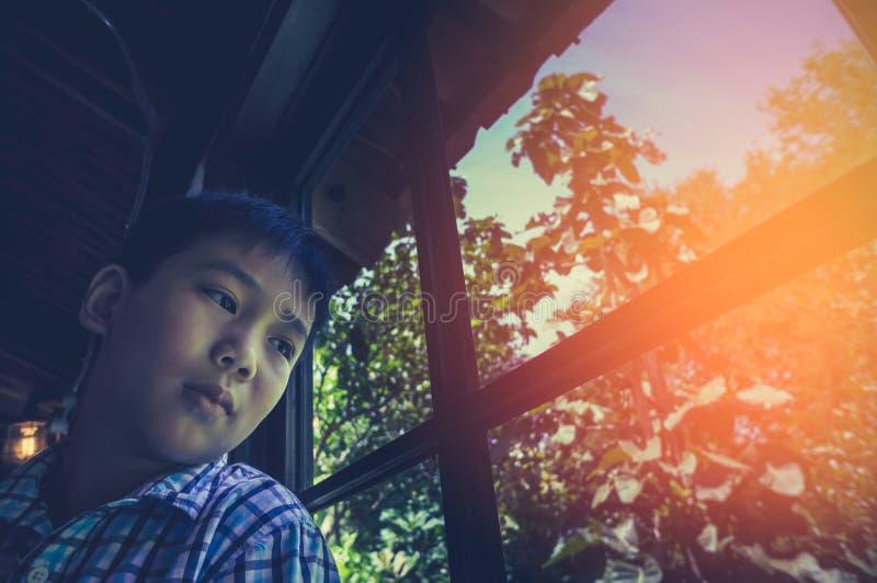 Criança asiática que senta-se perto da janela e que olha de lado ao sentir triste imagem de stock