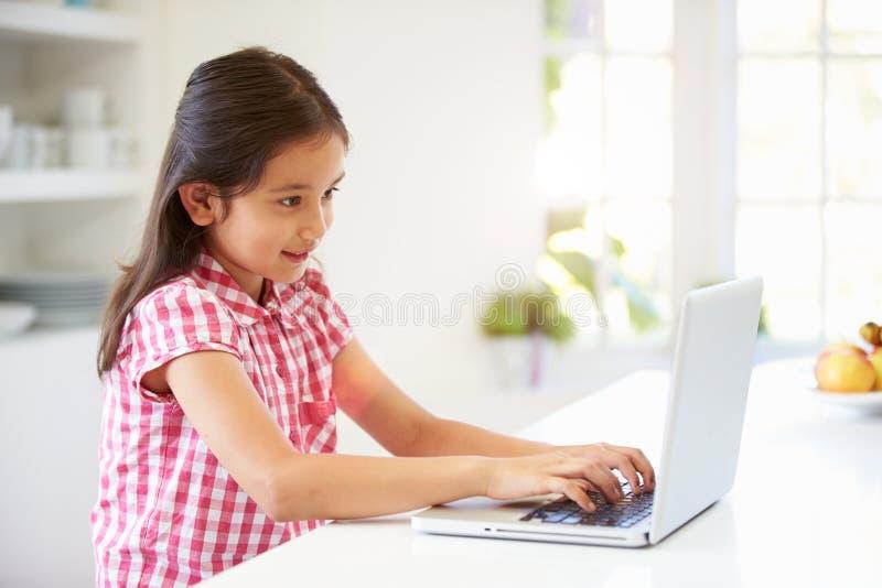 Criança asiática que usa o portátil em casa fotografia de stock royalty free