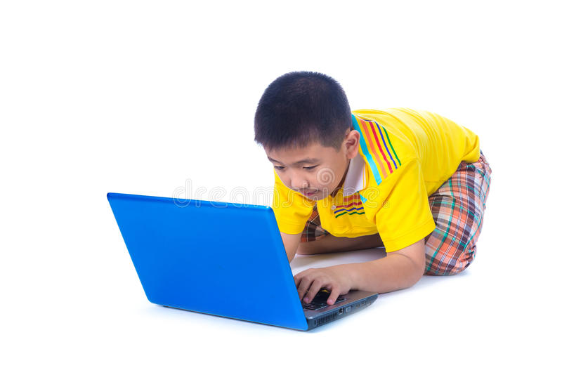 Criança asiática que usa um portátil, sentando-se no fundo branco, isolado foto de stock