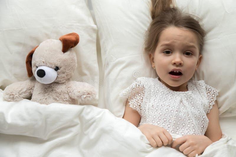 Criança assustado que encontra-se na cama com o brinquedo receoso do pesadelo imagem de stock