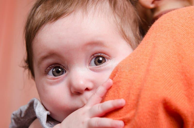 Criança assustado que esconde atrás do ombro da mamã imagens de stock royalty free