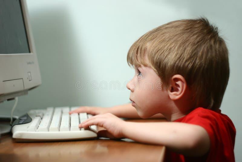 A criança atrás de um computador.