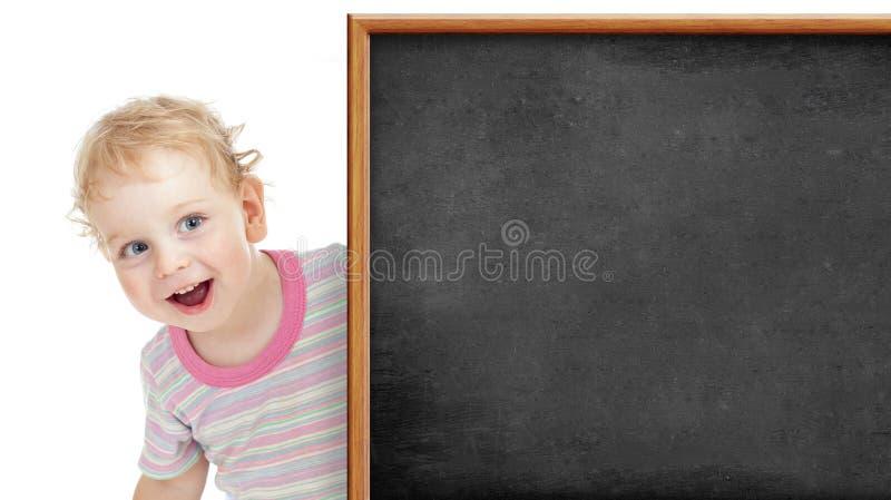 Criança atrás do quadro-negro vazio fotos de stock royalty free