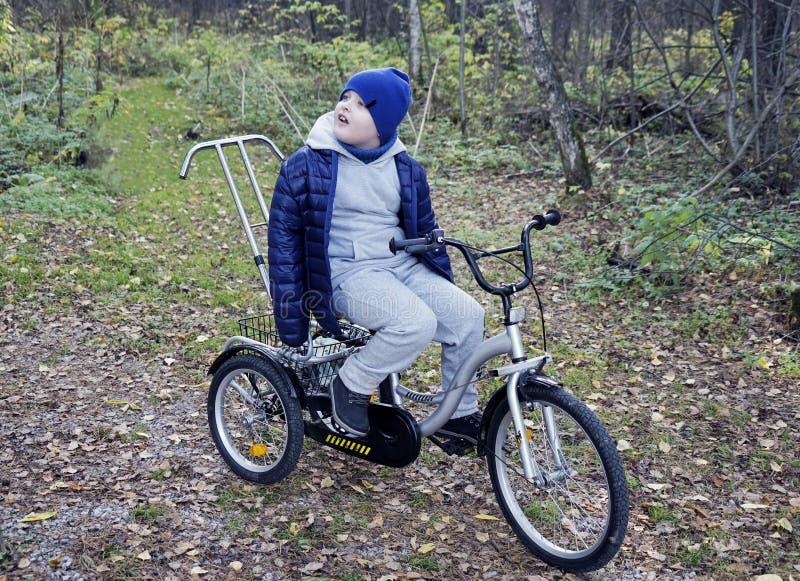 Criança autística com inabilidades em um triciclo com gestão para a mamã, em um tampão azul e em um revestimento no parque para u fotografia de stock royalty free