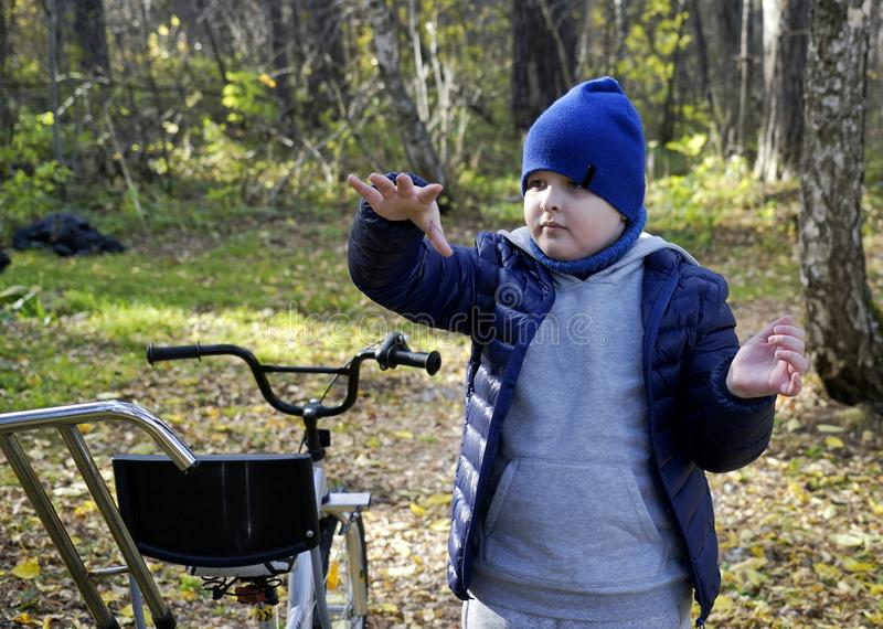 Criança autística com inabilidades em um triciclo com gestão para a mamã, em um tampão azul e em um revestimento no parque para u fotos de stock