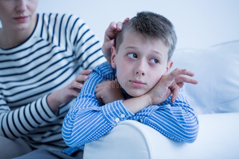 Criança autística que encontra-se no sofá fotografia de stock