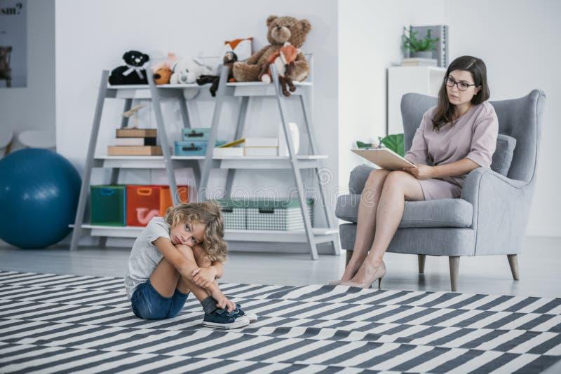 Criança autística que senta-se em um tapete em uma sala de aula quando seu coun imagem de stock royalty free