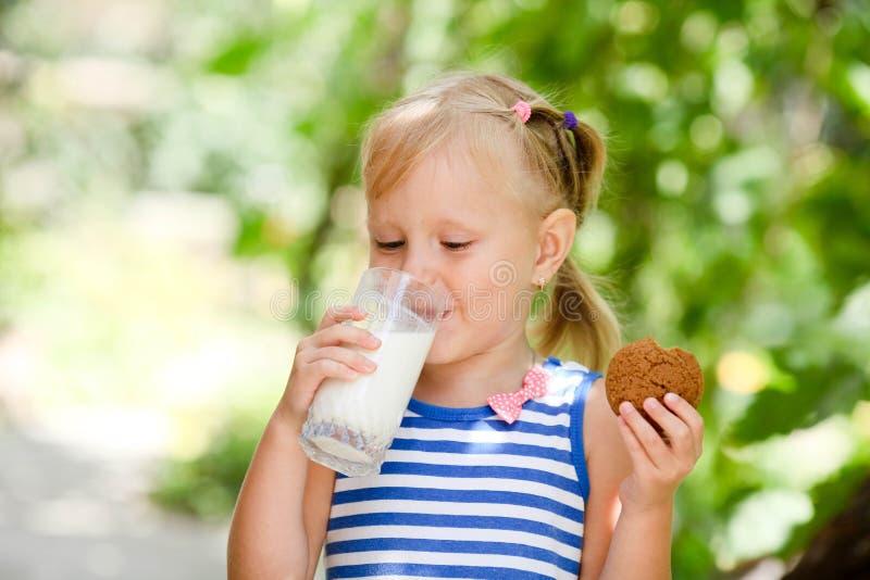 A criança bebe o leite e come cookies fora foto de stock