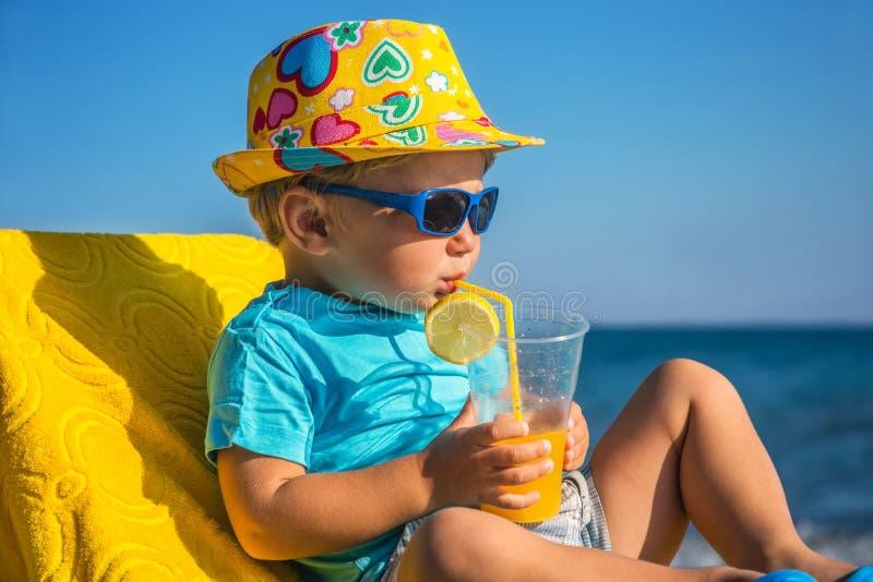 A criança bebe o suco contra o mar fotos de stock royalty free
