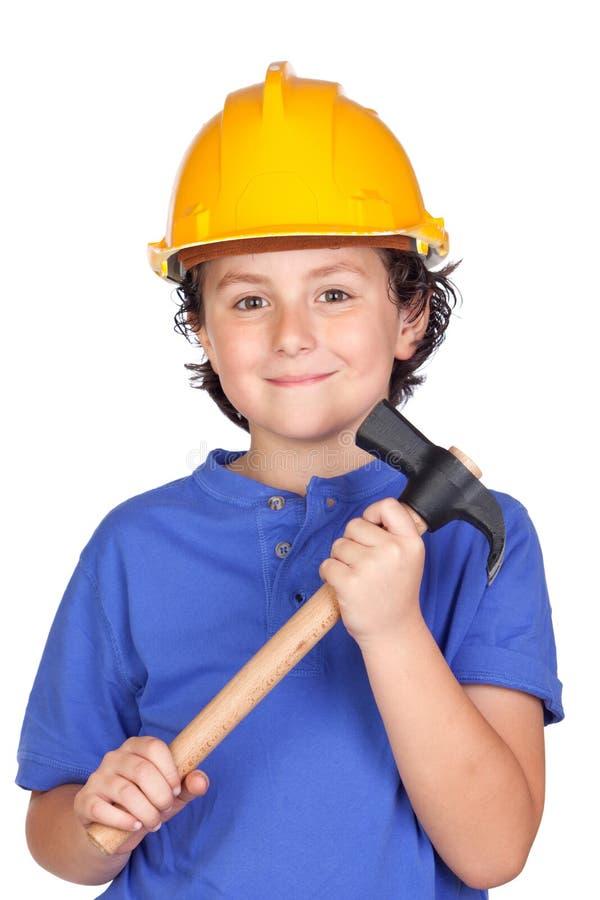 Criança bonita com capacete e o martelo amarelos imagens de stock