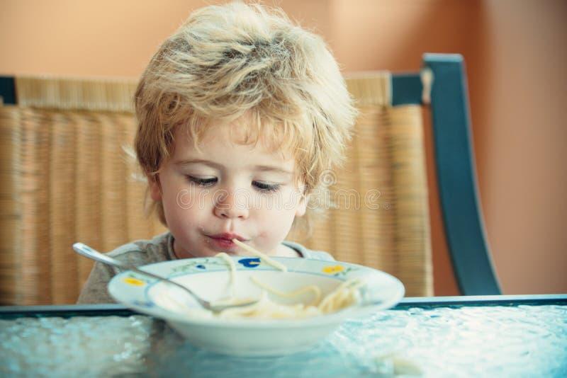 Criança bonita com espaguete Engraçado come macarrão Almoço para pré-escolarização imagem de stock royalty free