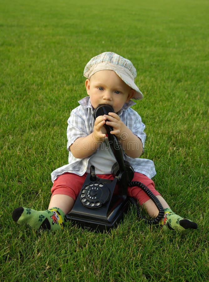 Criança bonita com o telefone na grama verde foto de stock royalty free