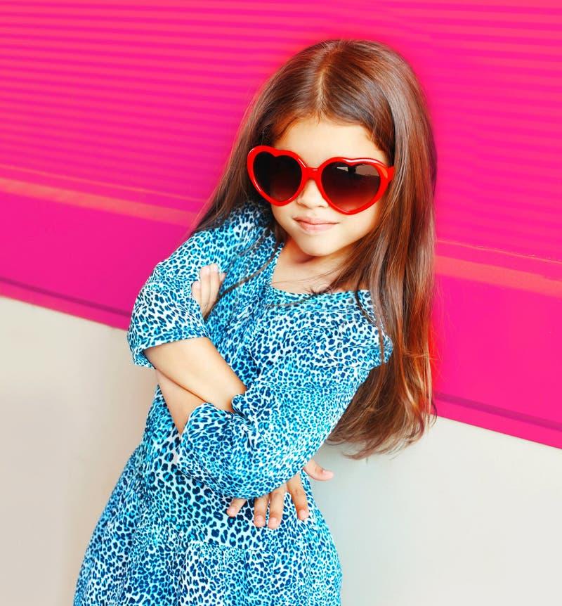 Criança bonita da menina do retrato em óculos de sol vermelhos da forma do coração no rosa colorido foto de stock