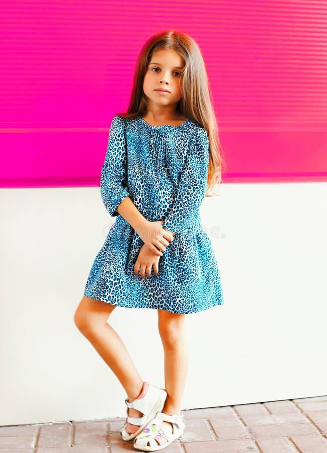 Criança bonita da menina no vestido do leopardo na parede cor-de-rosa colorida fotos de stock royalty free
