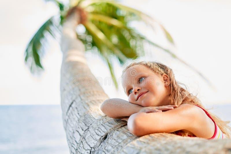 A criança bonita de sonho feliz relaxa na praia tropical com palmeira imagens de stock
