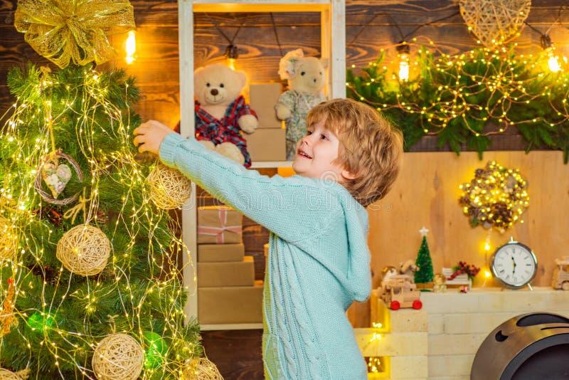 Criança bonita decorando árvore de Natal com bauble Preparação do Natal, garoto engraçado celebrando Ano Novo Natal fotografia de stock