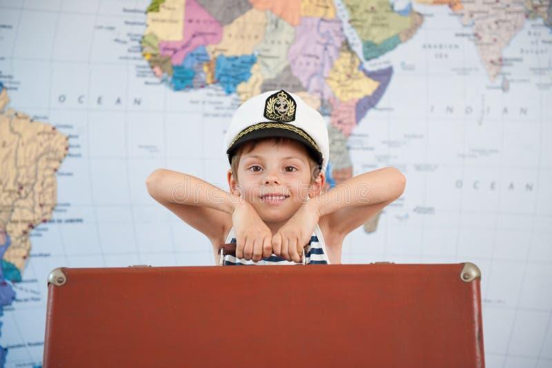 Criança bonita feliz no chapéu do capitão com a mala de viagem pesada no fundo do mapa do mundo fotos de stock