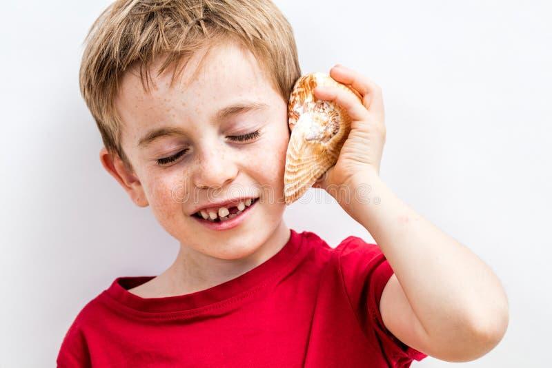 Criança bonita imaginativa de sorriso que escuta o oceano em um shell imagem de stock