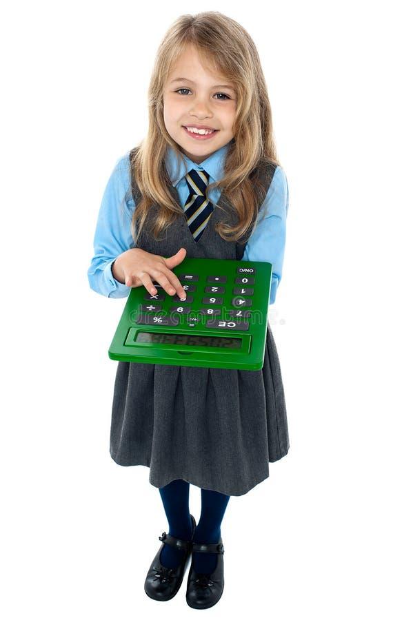 Criança bonita na farda da escola usando a calculadora fotos de stock royalty free