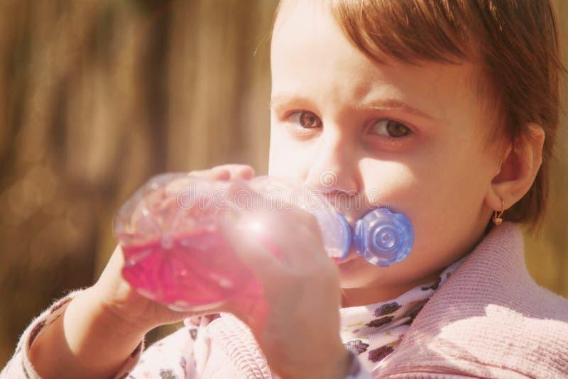 Criança bonita pequena da menina que bebe o suco natural saboroso exterior imagem de stock royalty free