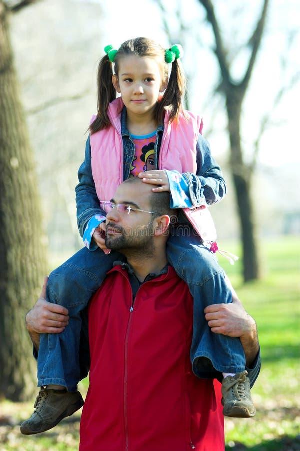 Criança bonita pequena no ombro do pai fotos de stock