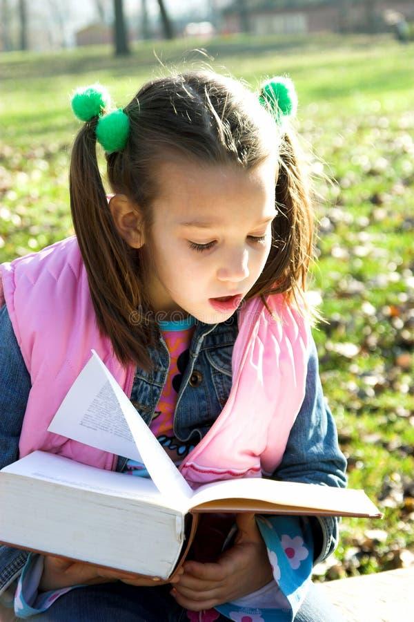 Criança bonita pequena que lê o livro fotos de stock