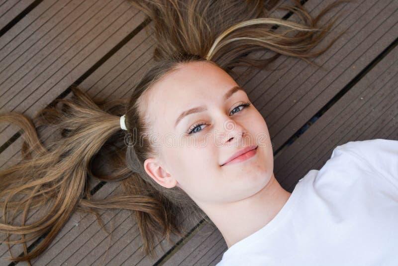 Criança bonita positiva alegre, menina adolescente da idade, estar no grande humor e mostrar seus sorriso e caudas longas do cabe imagens de stock royalty free