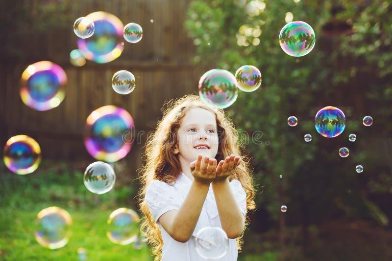 Criança bonita que aprecia fundindo bolhas de sabão foto de stock