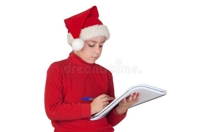 Criança bonita que escreve sua letra do Natal imagens de stock