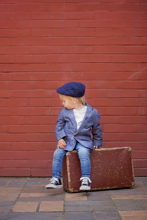 Criança bonitinha, sentada numa mala vintage em frente à parede de tijolos vermelhos, vestida e casual inteligente foto de stock royalty free