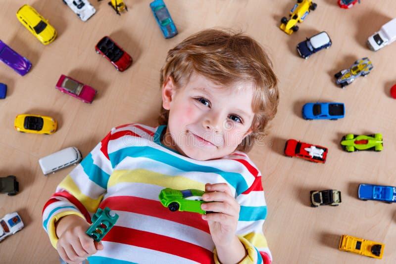 Criança bonito adorável com lote de carros coloridos diferentes do brinquedo foto de stock royalty free