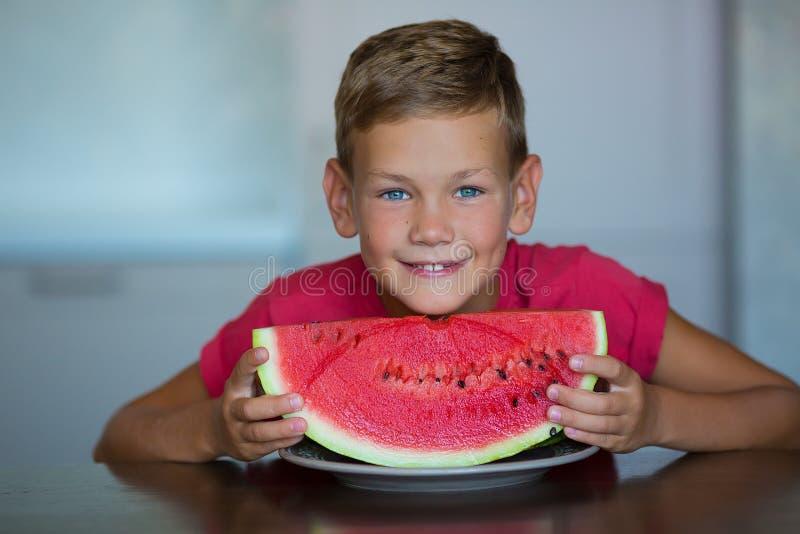 A criança bonito aprecia da melancia suculenta do fruto de baga do verão o menino considerável dos olhos azuis que veste o t-shir imagem de stock royalty free