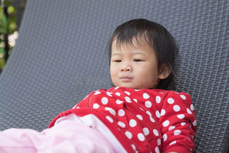 A criança bonito asiática da menina está furando no sofá moderno imagem de stock royalty free