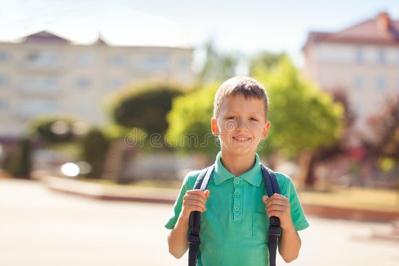 A criança bonito com mochila vai à escola Menino com backpak imagem de stock