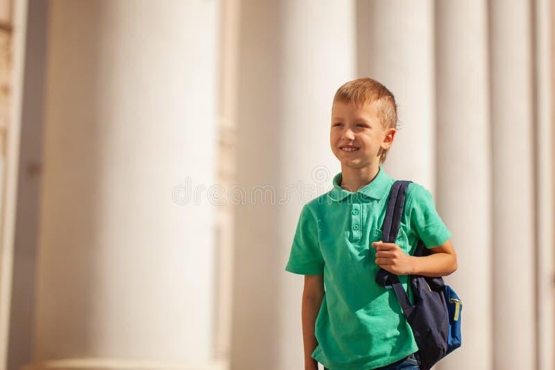 A criança bonito com mochila vai à escola Menino com backpak fotos de stock