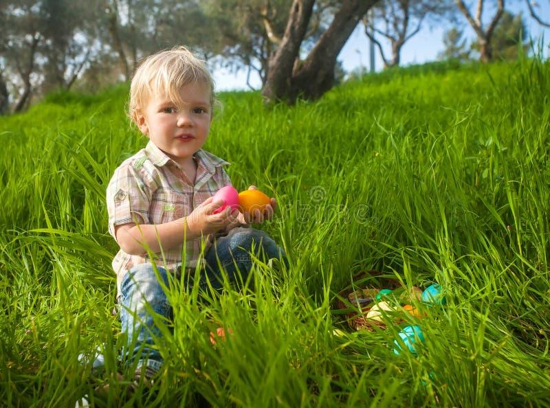 Criança bonito com os ovos da páscoa na grama imagem de stock royalty free