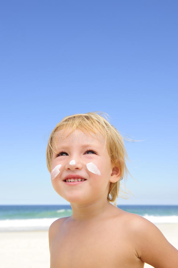 Criança bonito com protecção solar na praia imagens de stock royalty free