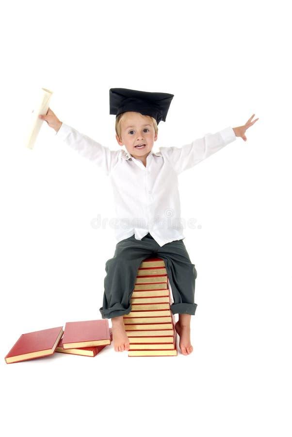 Criança bonito com tampão e diploma da graduação imagens de stock