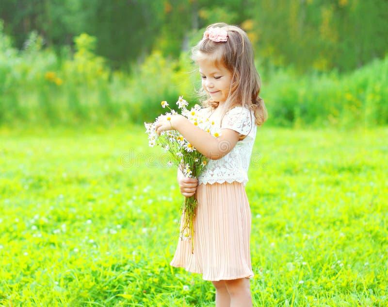 A criança bonito da menina com camomilas do ramalhete floresce no verão fotografia de stock