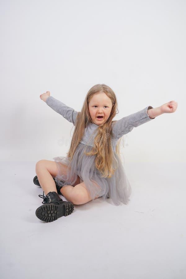 Criança bonito da menina com o cabelo louro longo que senta-se no assoalho e nos bocejos docemente, esticando suas mãos em sent imagens de stock