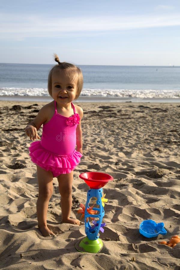 Criança bonito da menina na praia que joga na areia com brinquedos foto de stock royalty free