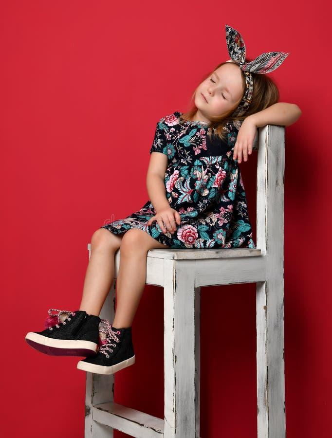 Criança bonito do bebê no vestido e na faixa do verão da forma que sentam-se no pensamento da cadeira fotografia de stock